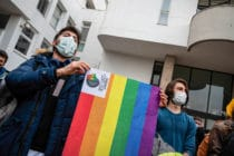 Demonstrators wearing masks hold an LGBT+ flag during the demonstration at Boaziçi University, Istanbul, Turkey