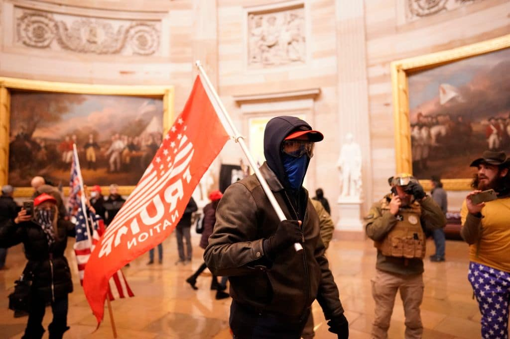 Protester holds a Trump flag during violent insurrection at US Capitol
