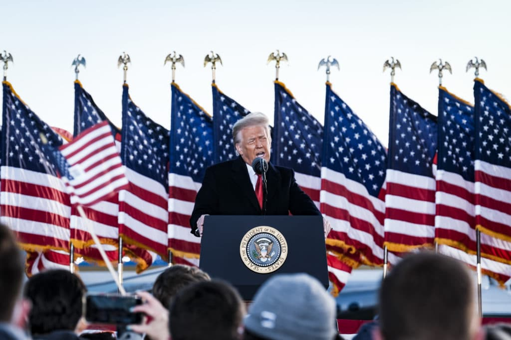 President Donald Trump speaks to his supporters on stage, American flags behind him