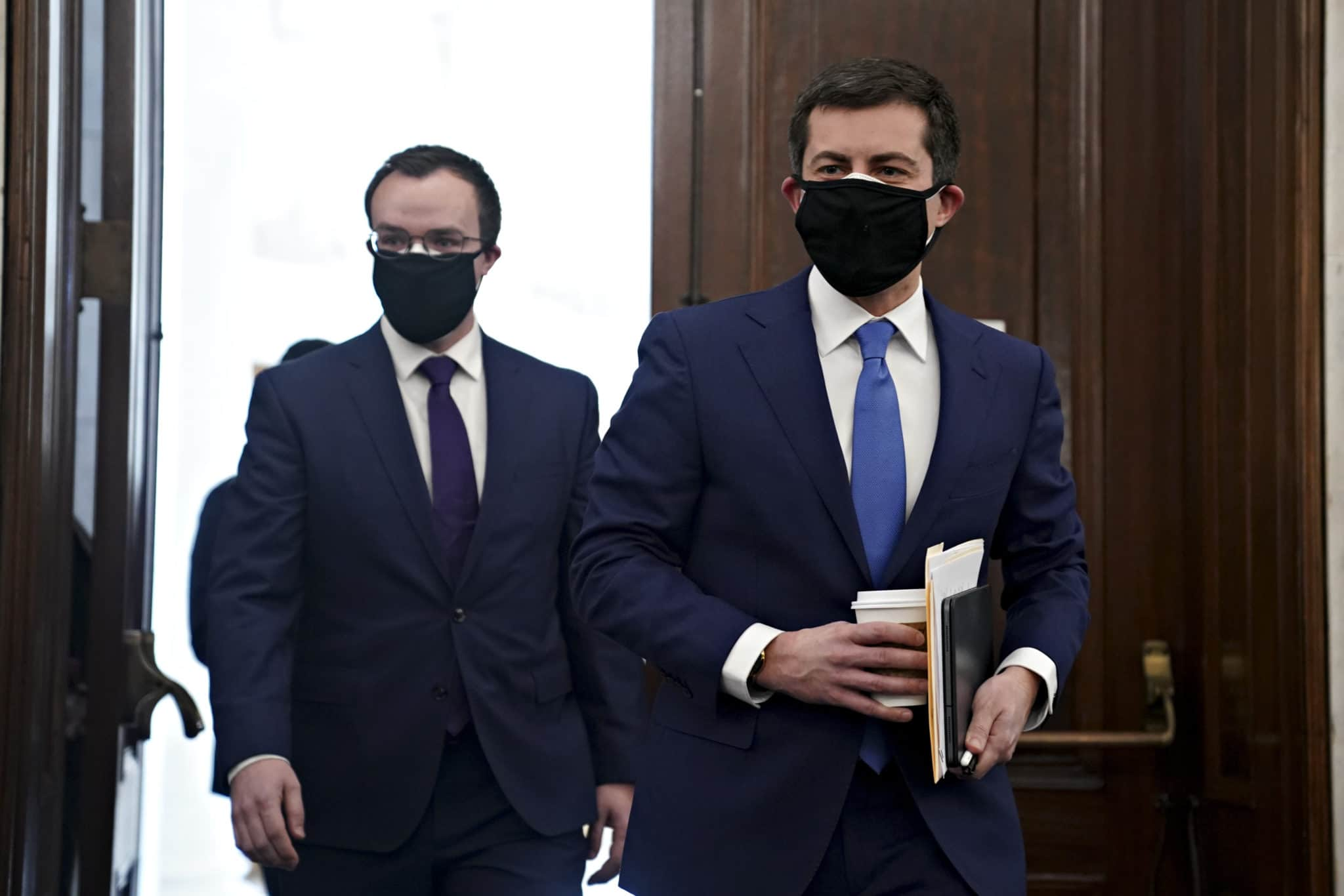 Pete Buttigieg and Chasten Buttigieg, both wearing suits, walk through the doors in the Senate