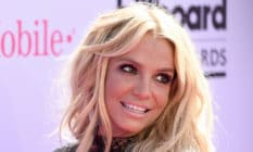 Britney Spears turns to the left while smiling in a black dress