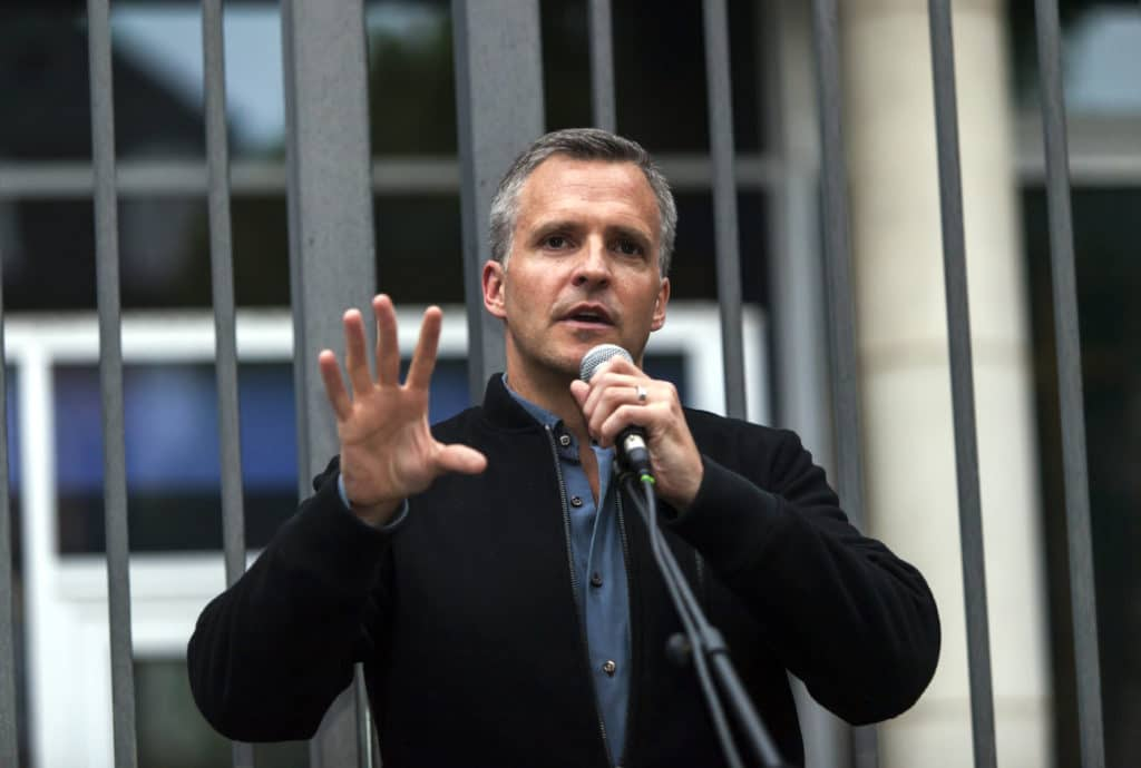 Rufus Gifford speaks into a microphone in a blue shirt and dark blazer