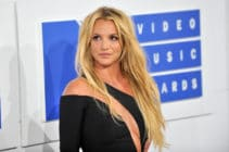 Britney Spears turns to the right in a black dress