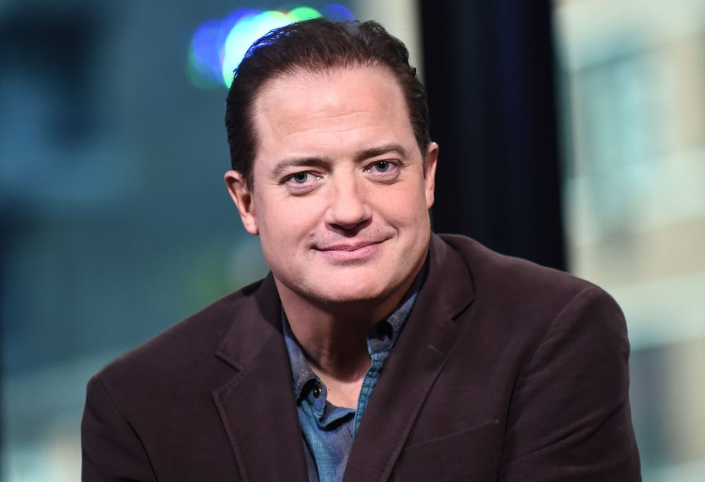 Brendan Fraser smiles at the camera in a blue shirt and black blazer