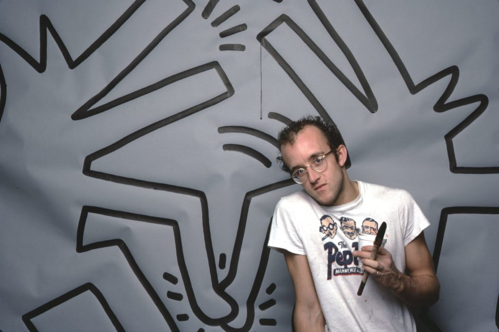 Keith Haring with one of his art works