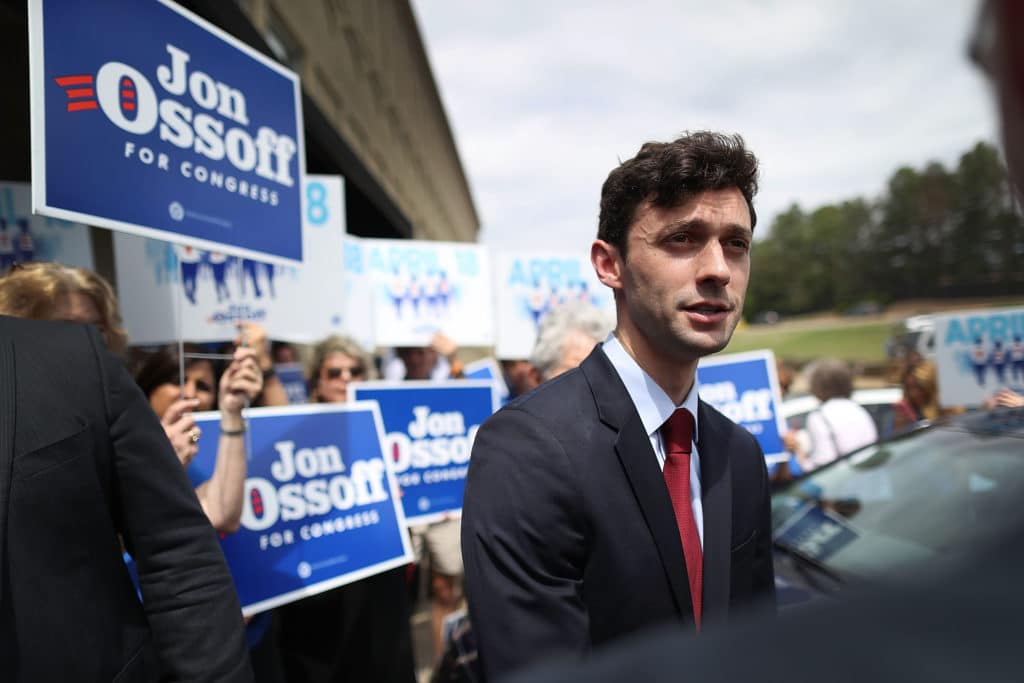 Jon Ossoff in a suit speaks to reporters while supporters hold up signs