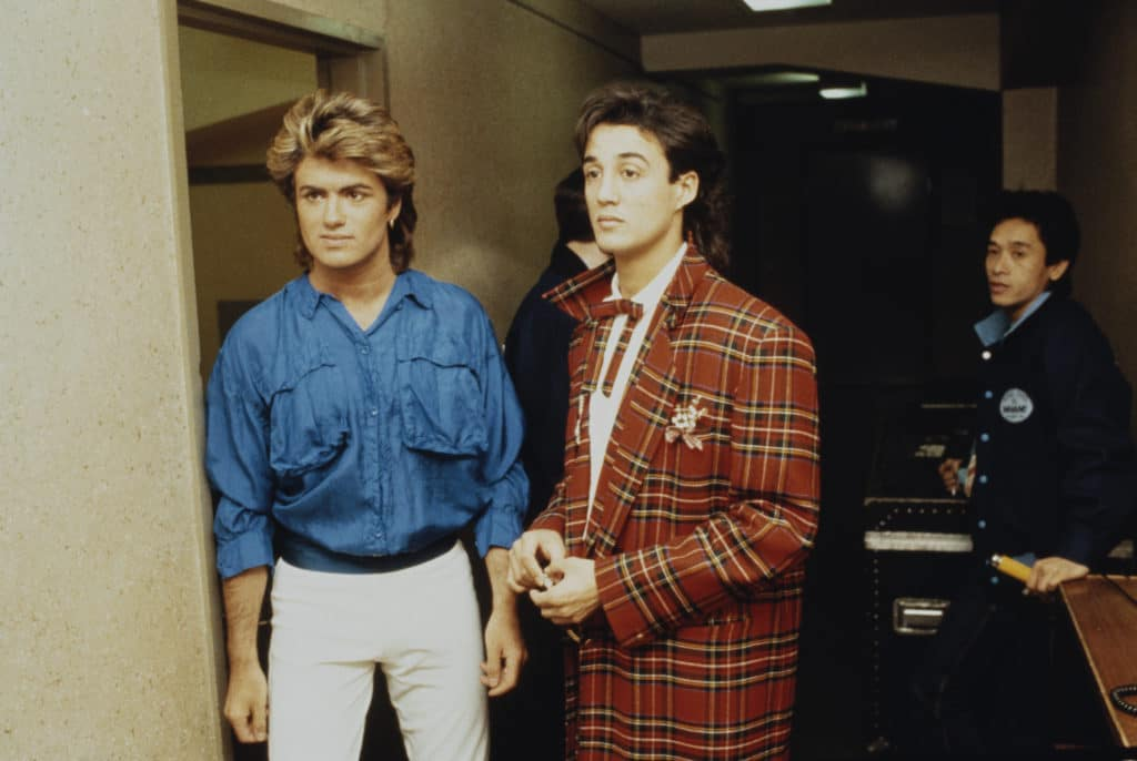 George Michael in a denim shirt and white jeans and Andrew Ridgeley in a tartan suit