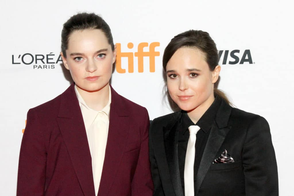 Emma Portner in a burgundy suit and Elliot Page in a black suit and white tie