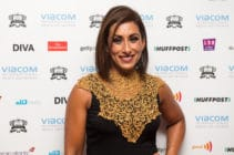 Saira Khan poses in a gold and black dress