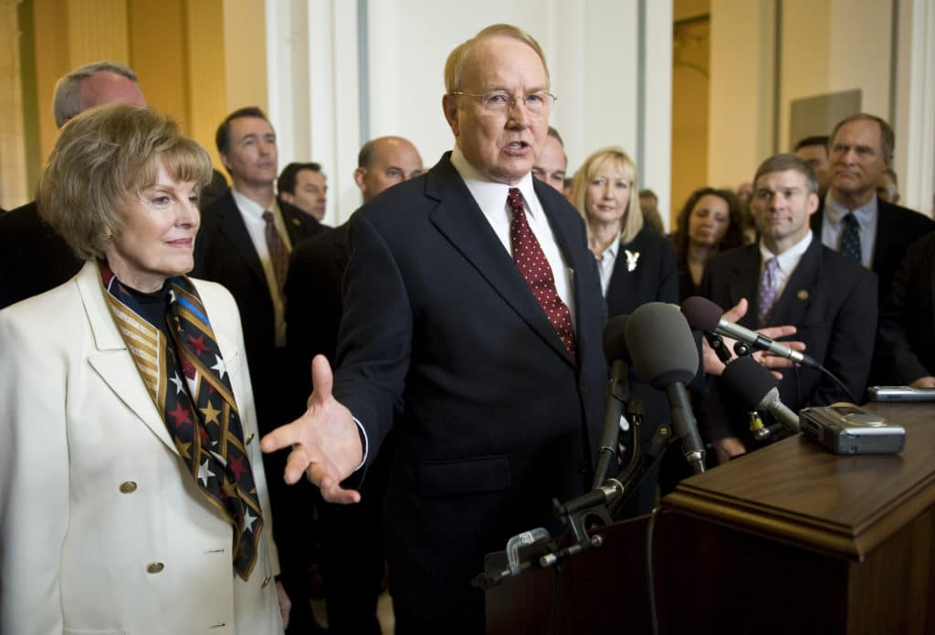 James Dobson in a red tie and black suit standing by his wife Shirley Dobson (L)