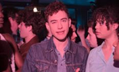 Olly Alexander surrounded by friends in a bar
