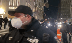 NYPD officers outside Trump Tower. One is close to the camera wearing a face mask