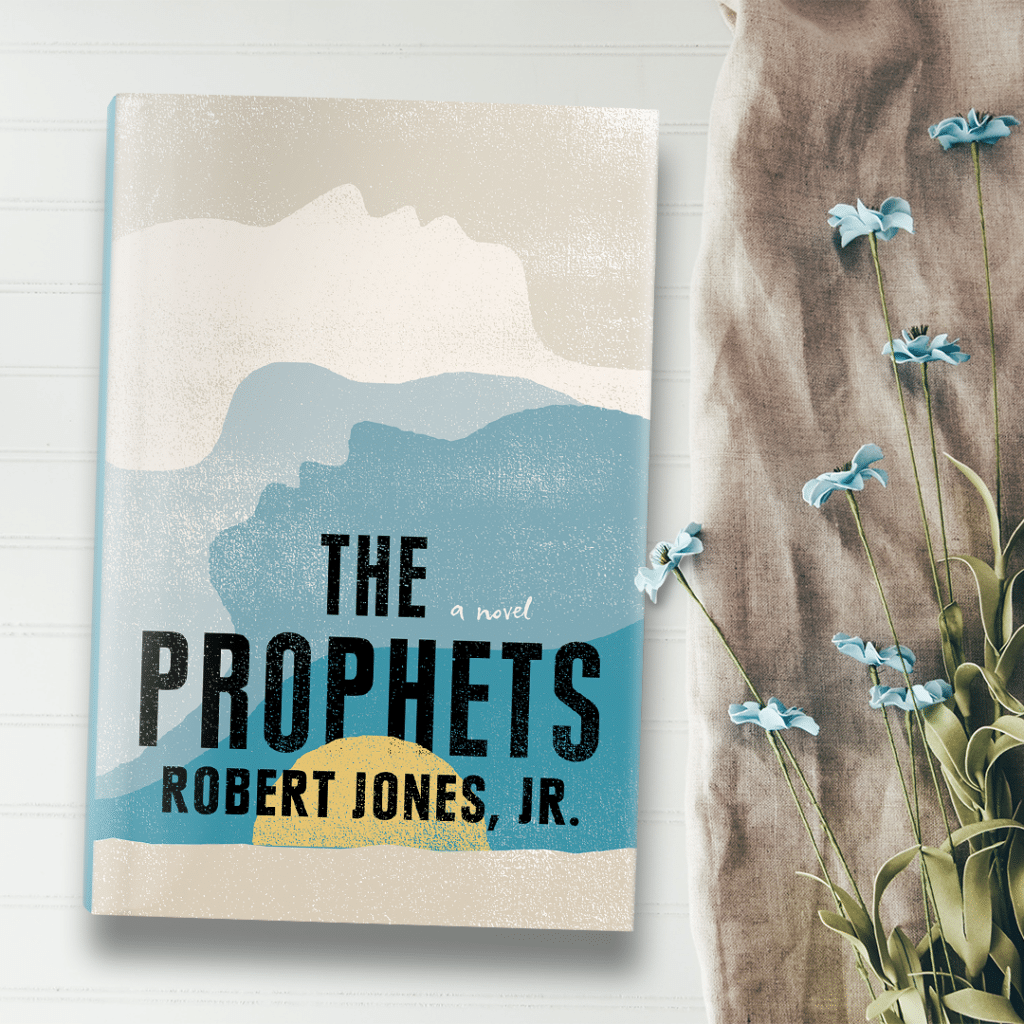 A hardback copy of The Prophets. Its cover is a simple illustration of a sunset. Next to the book are blue flowers.