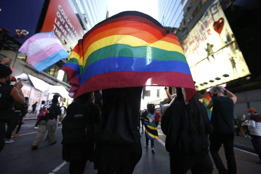 Americans holding a pride flag and trans flag in the background during a protest.