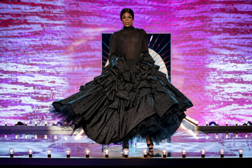 Asttina in a long sheer dress with dramatic tiered skirt, in the style of Naomi Campbell