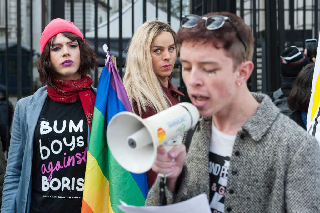 LGBT protestors, one wearing a 'bum boys against Boris' t-shirtm another holding a rainbow Pride flag