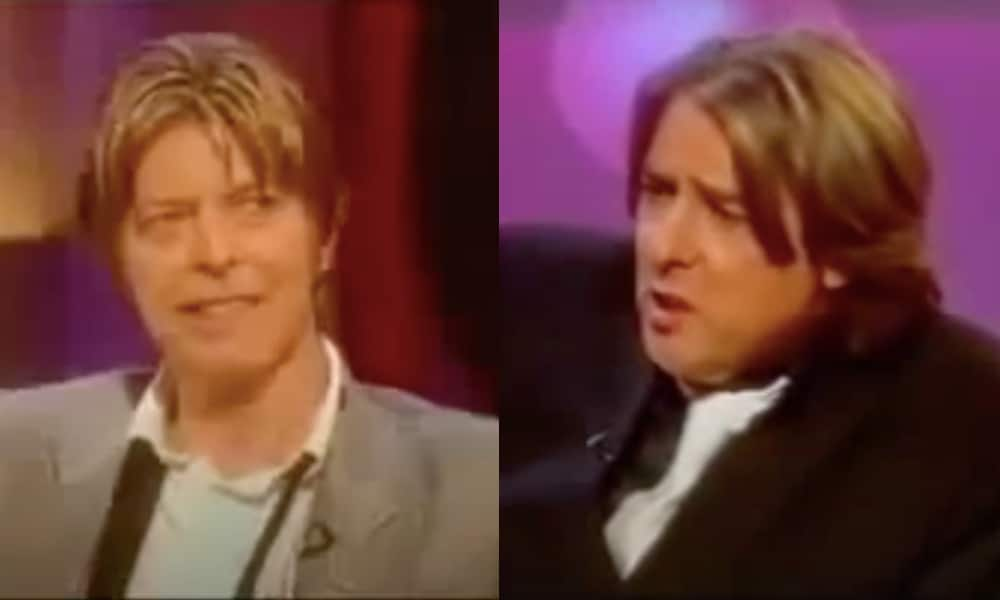 (L) David Bowie in a grey suit smiling. (R) Jonathan Ross in a black suit mid-speaking,