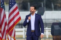 Donald Trump Jr speaking in front of American flags