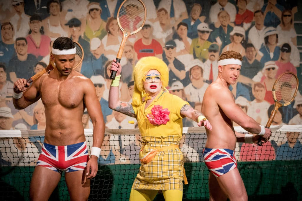 Ginny Lemon in a yellow suit holding a tennis racket, flanked by two Brit crew wearing just Union Jack boxers