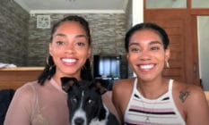 Kristen Gray and Saundra Alexander smile tot he camera with their dog