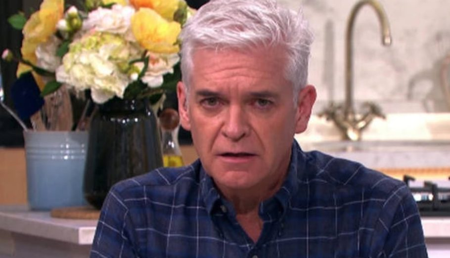 Philip Schofield looks unsettled at the camera while wearing a dark print shirt