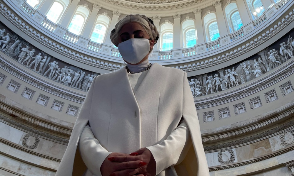 Lady Gaga in a white sheath cape and face mask, the rotunda of the Capitol complex framing her like a halo,
