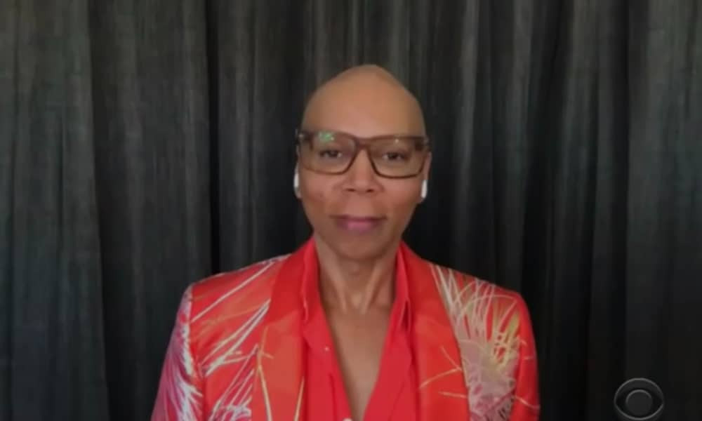 RuPaul out of drag, wearing glasses and a red shirt and blazer