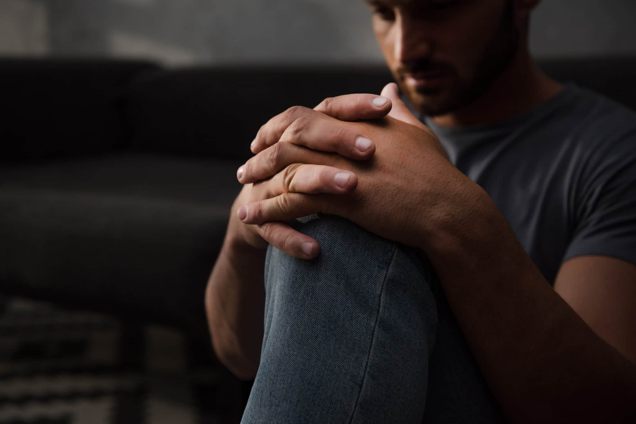A sad man sitting on floor at home, his hands on his knee
