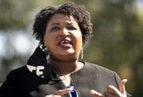 Close-up of Stacey Abrams speaking. A black face mask with 'VOTE' in bold white text is hanging from one ear.