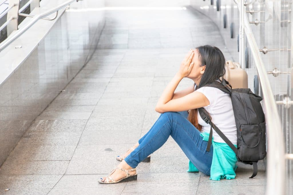 A woman sits on the floor with her hands on her face, crying, while wearing a backpack