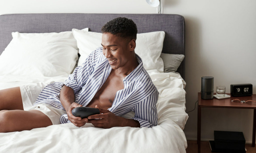 Man lying in bed in boxers and an open shirt holding the Arcwave Ion, a sleek sheath masturbator
