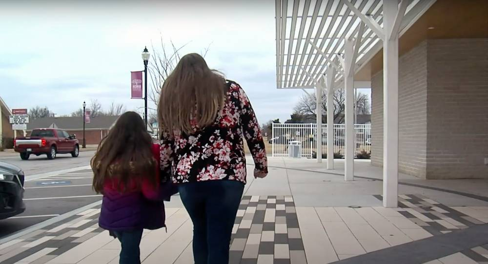 woman and her daughter walking together back portrait