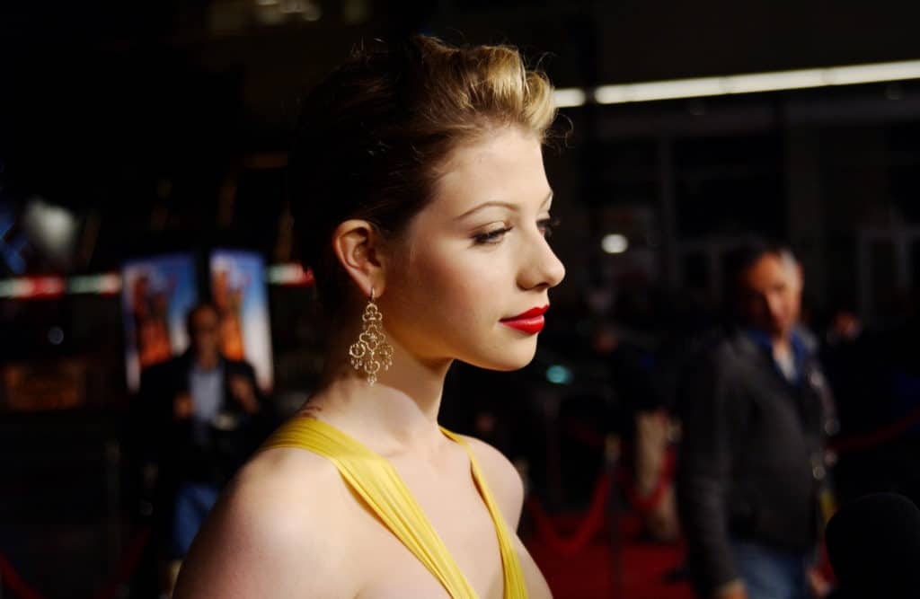 Michelle Trachtenberg in a yellow dress looks away from the camera on the red carpet