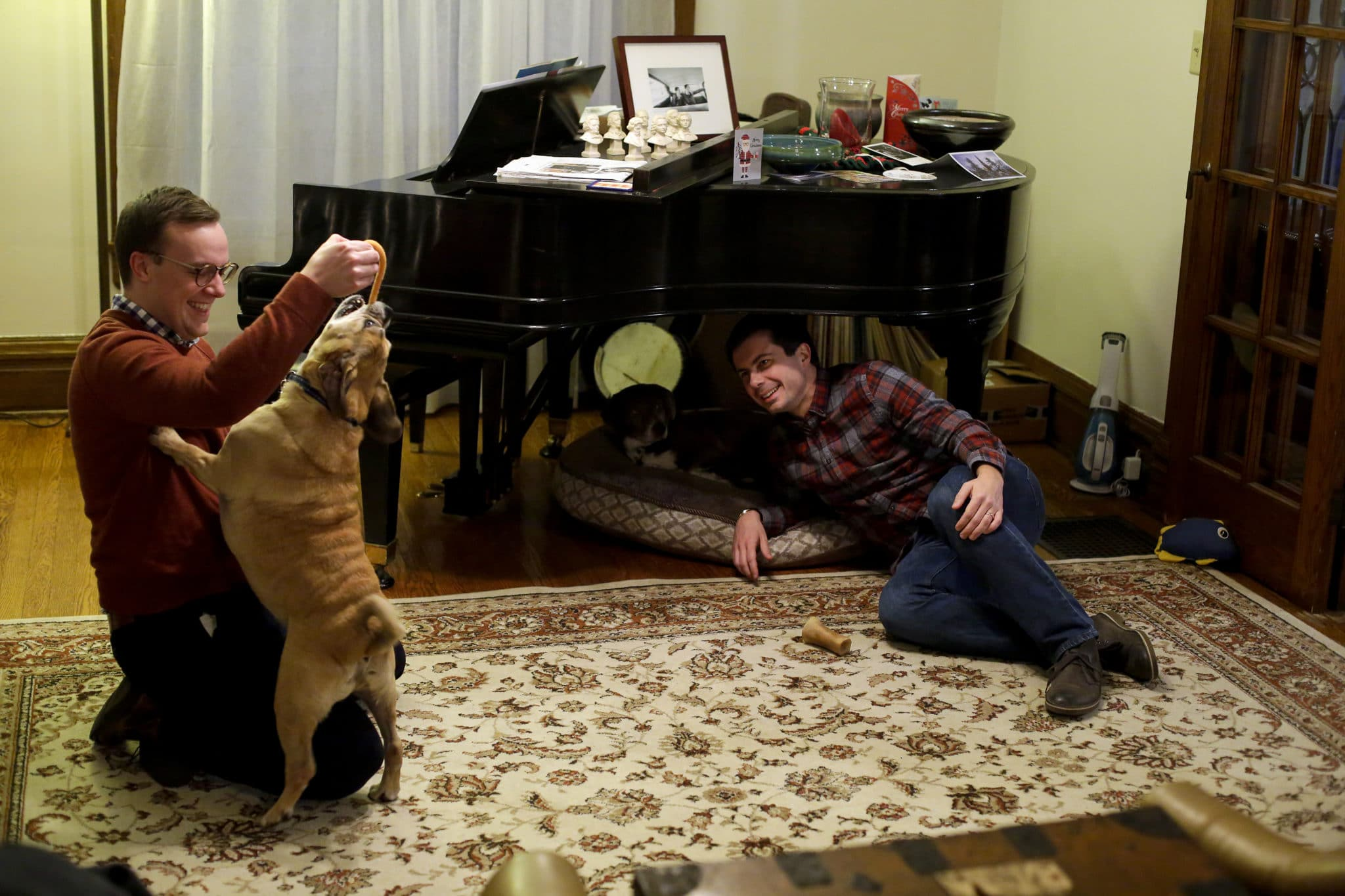 South Bend mayor Pete Buttigieg watches as his husband Chasten Glezman plays with their dog Buddy at their home on Tuesday
