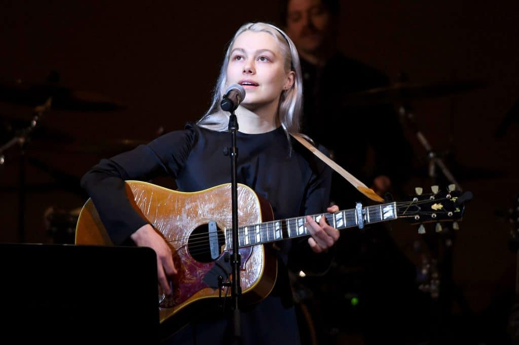 Phoebe Bridgers performs on stage holding a guitar