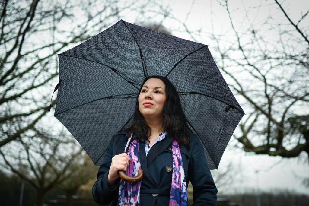 Monica Lennon holds an umbrella as she poses for a photograph