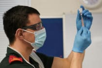 a paramedic draws up the AstraZeneca/Oxford University COVID-19 vaccine