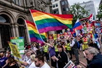 Thousands of members of the LGBTQ community march in the Birmingham Pride parade, holding rainbow flags and signs