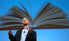 Amazon founder Jeffrey Bezos speaks in front of an image of an opened book