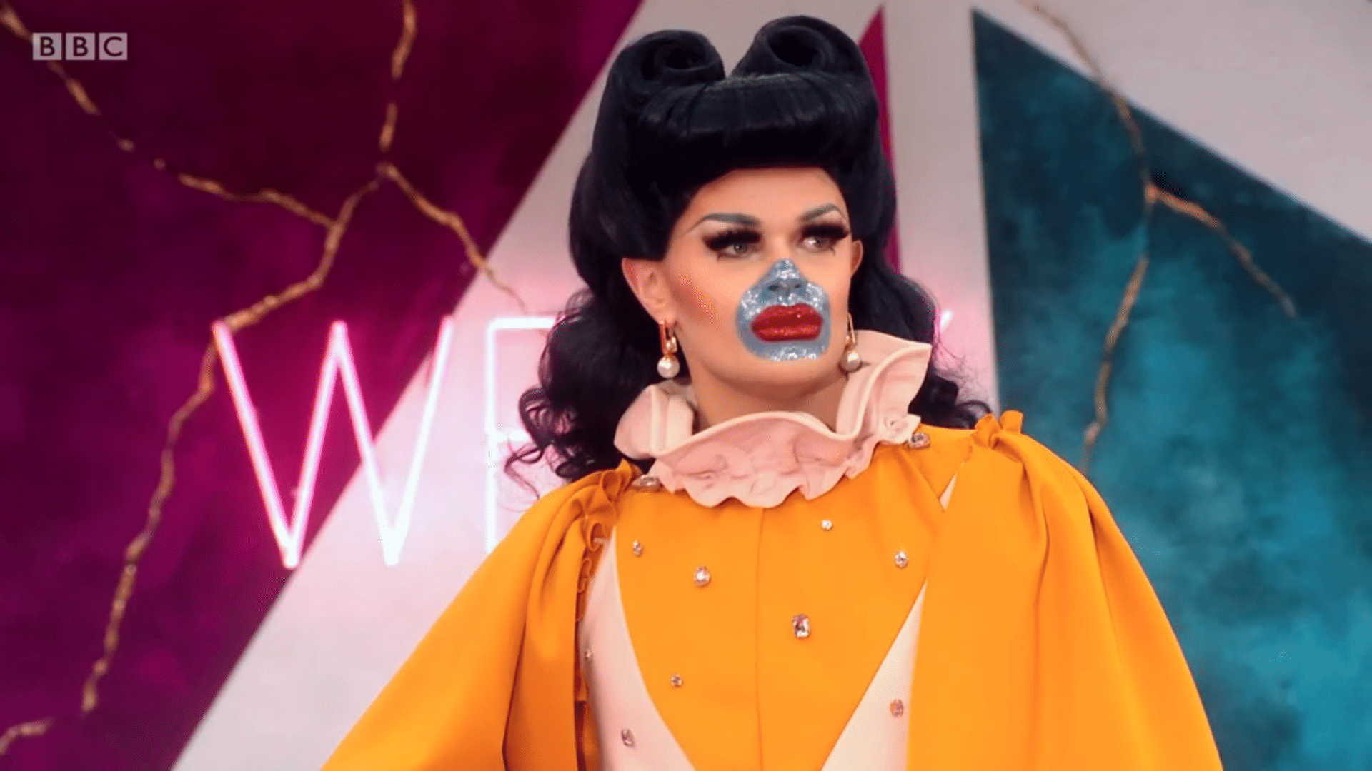 Sister Sister: a drag queen with a bright blue circle over her mouth and nose, wearing a yellow frilly dress and victory rolls in her hair