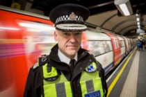 Adrian Hanstock, a police officer wearing a yellow h-vis vest, black jacket and tie and a police cap, standing on a Tube platform as a train speeds past