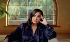 Demi Lovato in the trailer for her documentary, sitting on a chair resting her hand on her face