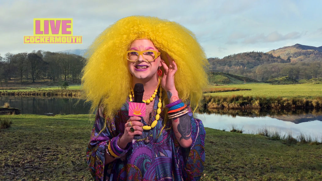 Ginny in a curly yellow wig and a paisley kaftan presenting the weather