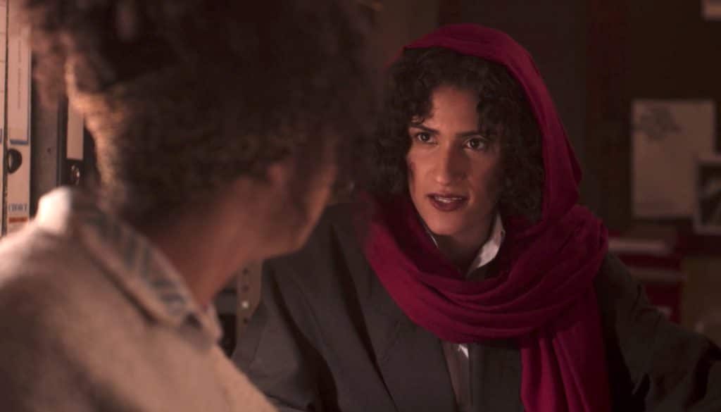 Lizbeth, in a dark suit and read headscarf, deep in conversation with Jill