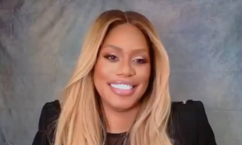 Laverne Cox smiles to the camera in a black top