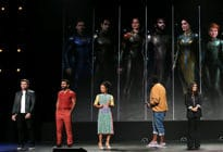 Richard Madden, Kumail Nanjiani, Lauren Ridloff, Brian Tyree Henry, and Salma Hayek on a stage infant of images of them in superhero costume