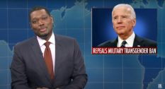 "Michael Che hosting Saturday Night Live's ""The Weekend Update"" with a picture of President Joe Biden in the background with text underneath reading 'repeals military transgender ban'"