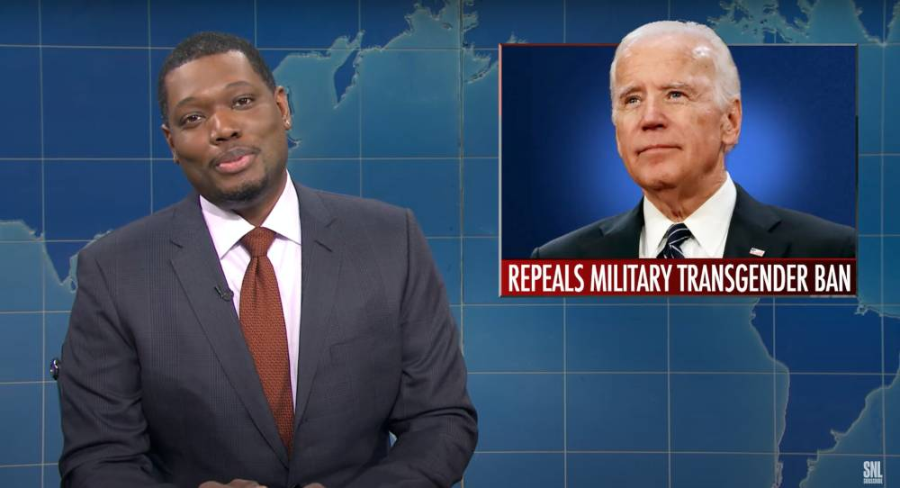 """Michael Che hosting Saturday Night Live's """"The Weekend Update"""" with a picture of President Joe Biden in the background with text underneath reading 'repeals military transgender ban'"""