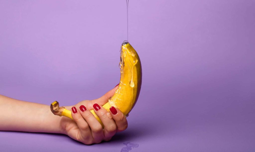 A banana being covered in honey