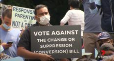 Man holding up sign that reads Vote against the change or suppression (conversion) bill